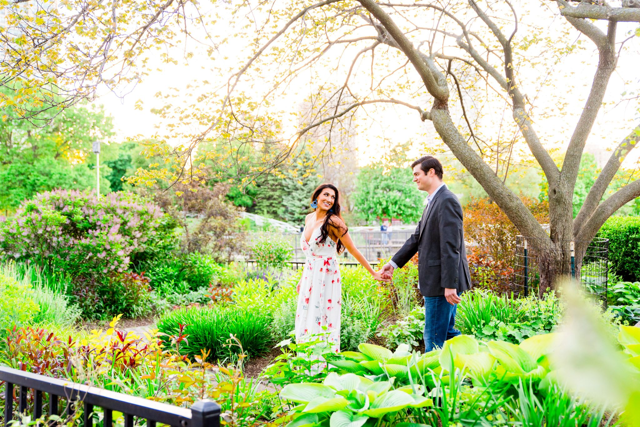 woman with long dark hair in a floral dress and blue macrame earrings leading fiance by the hand for engagement pictures