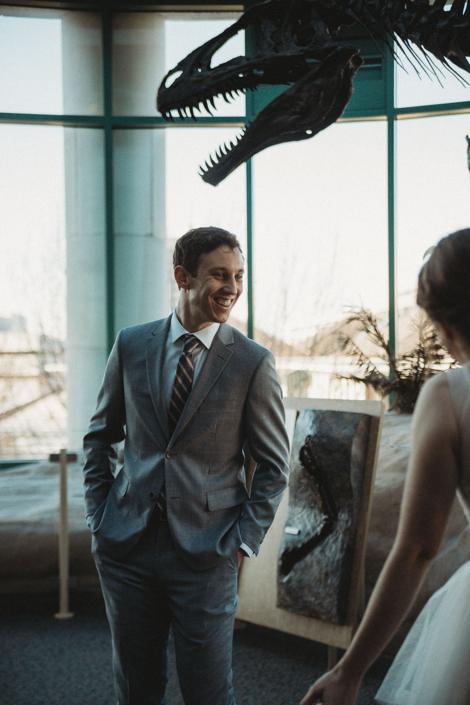 groom smiling while looking at bride in museum