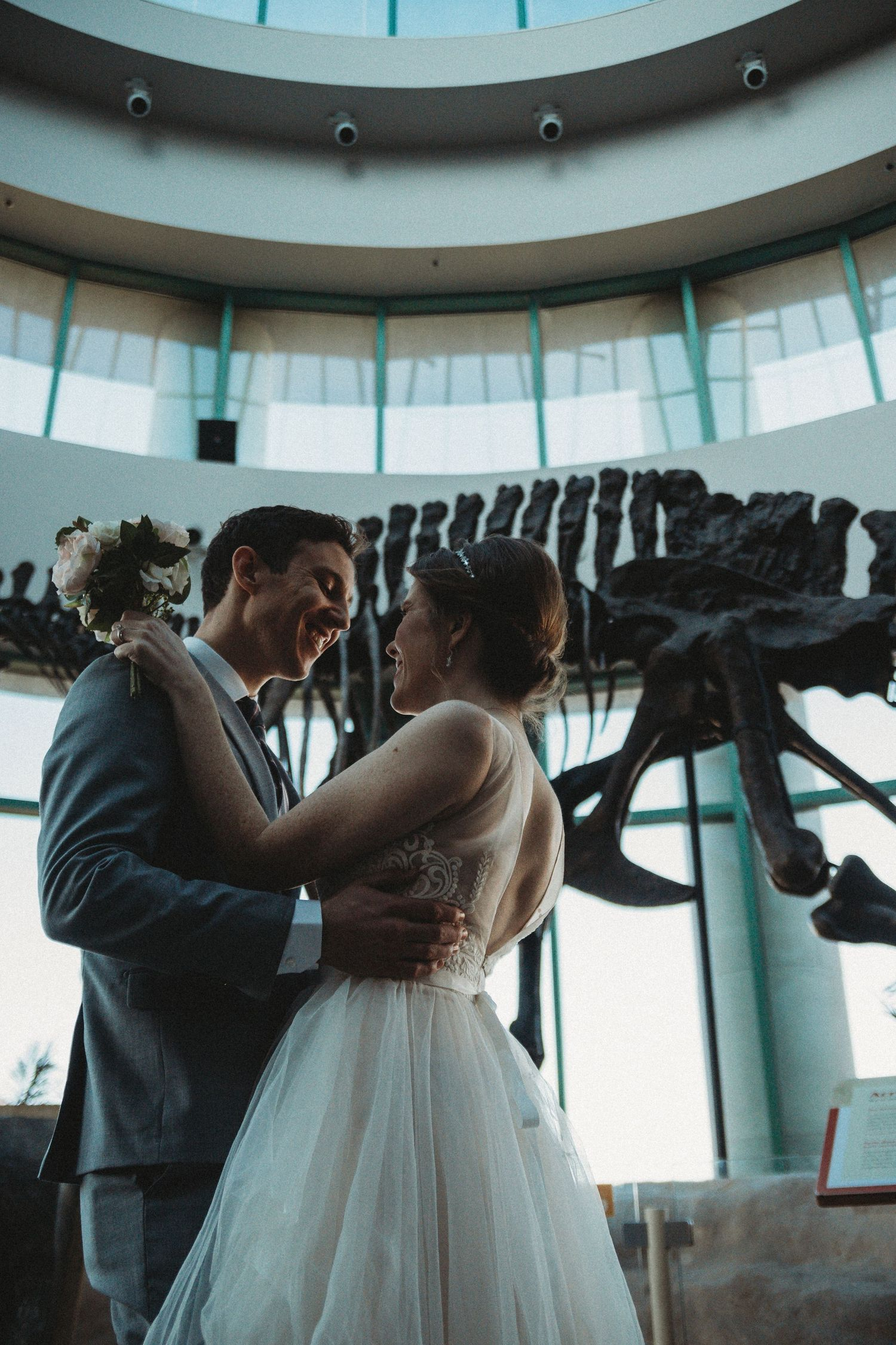 dinosaur bones behind bride and groom as they look at each other