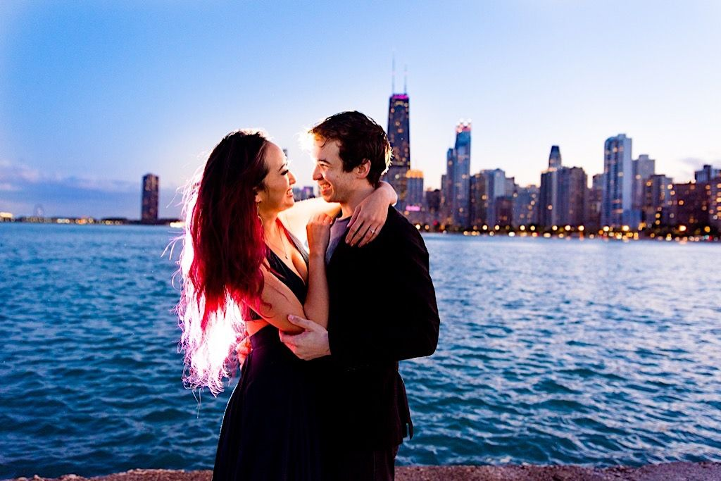 couple smiling at each other at night time with Chicago skyline behind them at North Avenue Beach