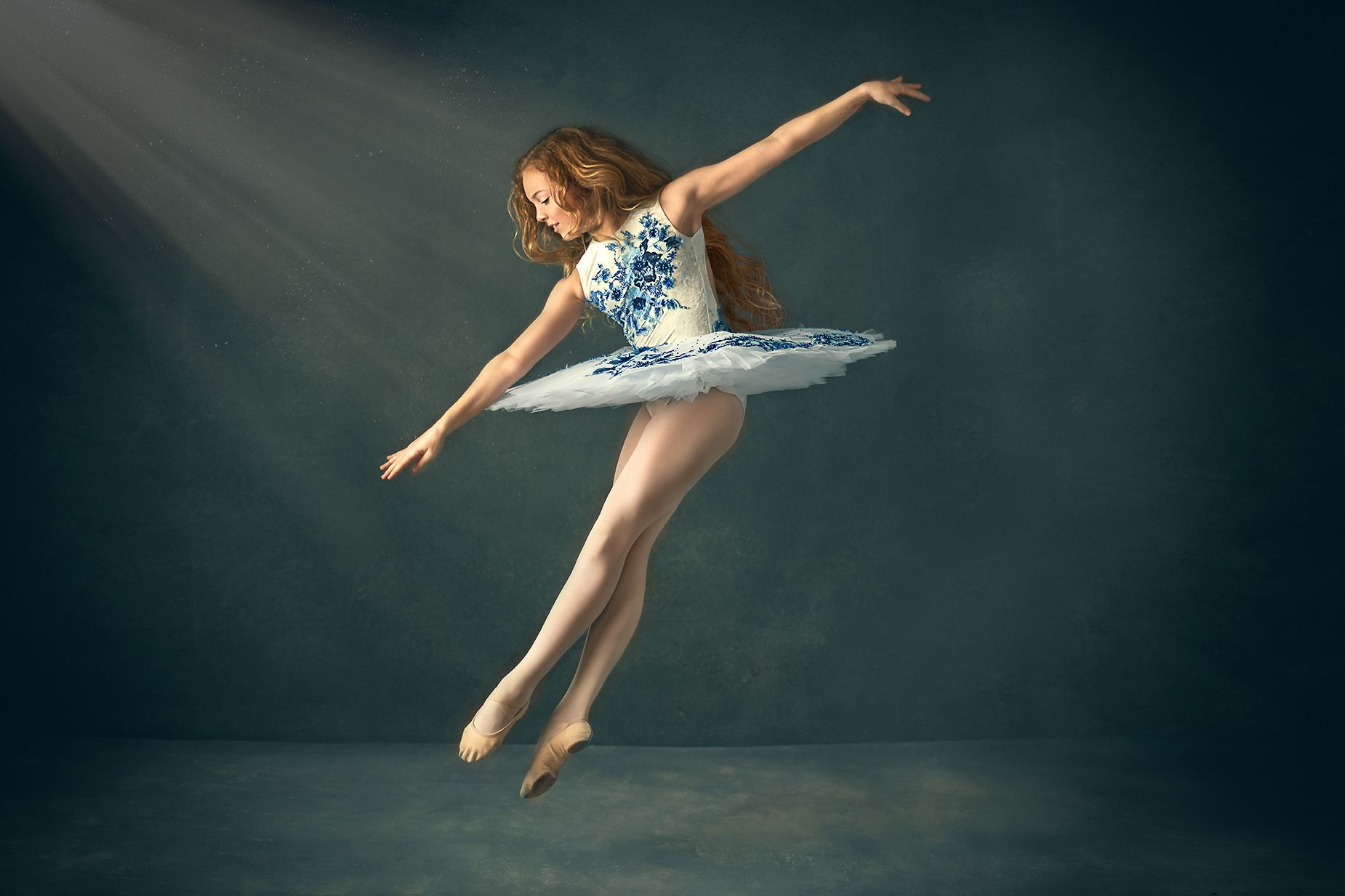 Dancer jumping in studio fine art session wearing tutu with beautiful lighting