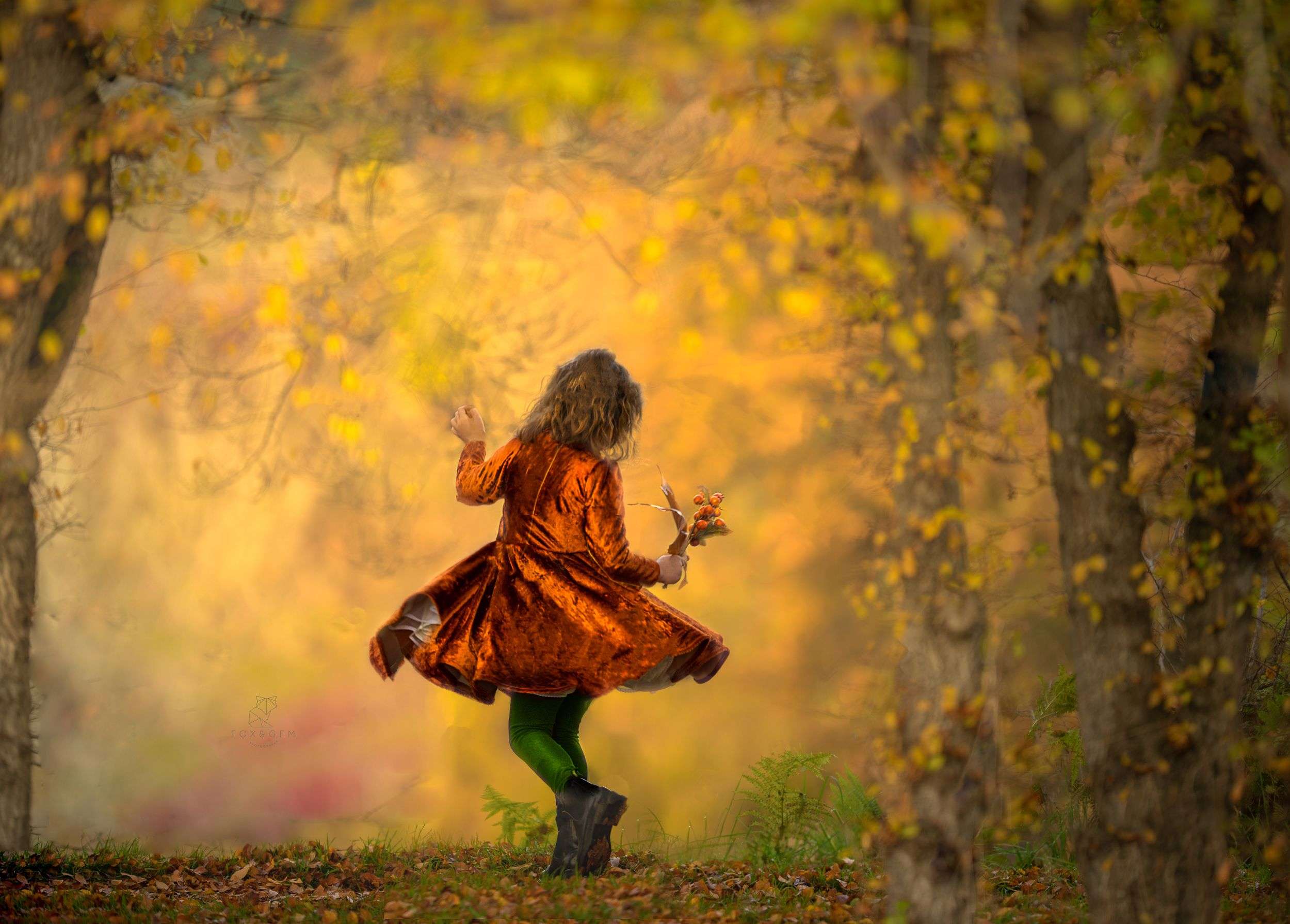 Small child dances in vintage style burnt orange dress in amazing outdoor painterly portrait in Victoria BC