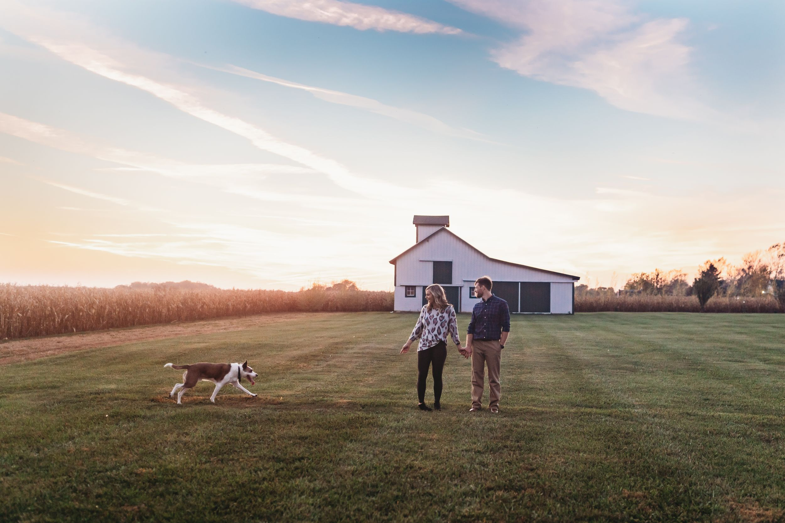 Couple playing in field with their dog in Marion, Indiana. Marion Indiana Family Photographer