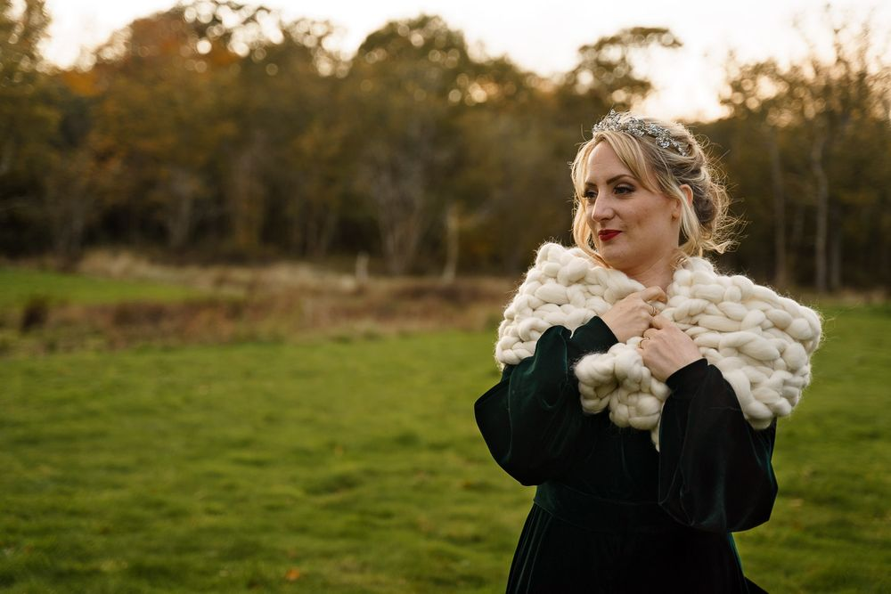 Bride snuggles up in a cosy wool shawl at her Hampshire winter wedding.