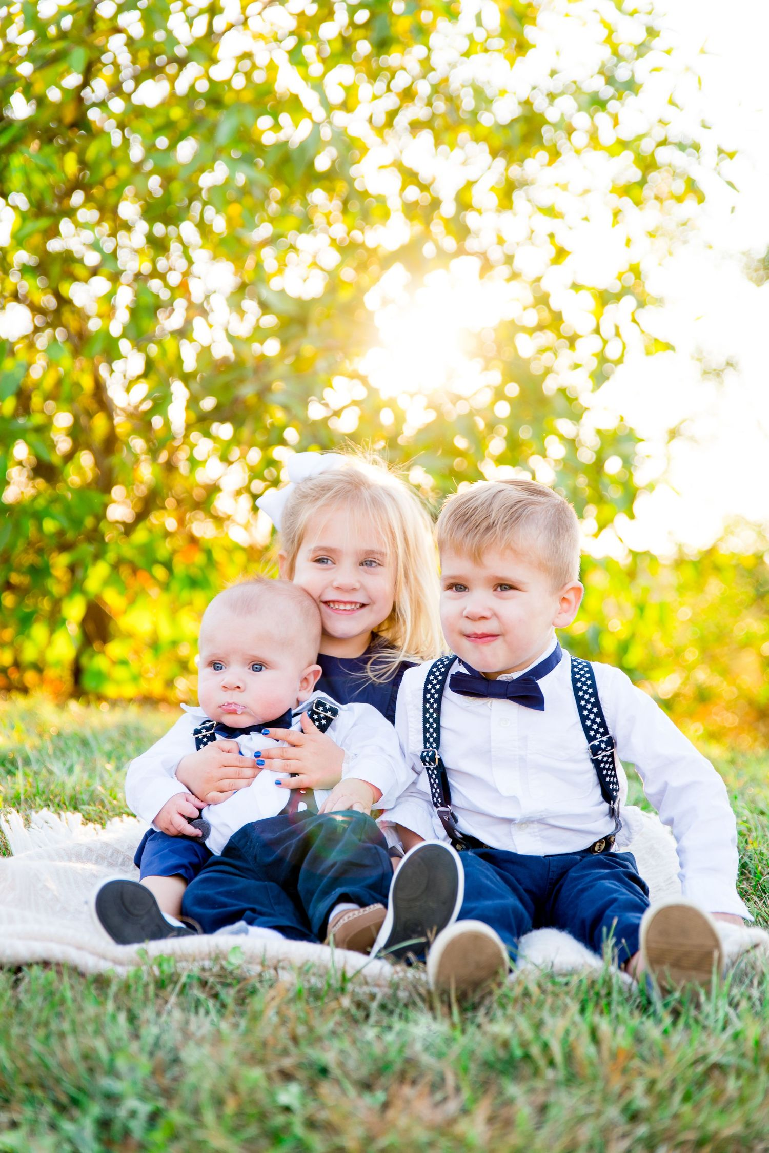 two young children and a baby boy wearing navy and white smiling in front of a blurry green bush at sunset in Chicago
