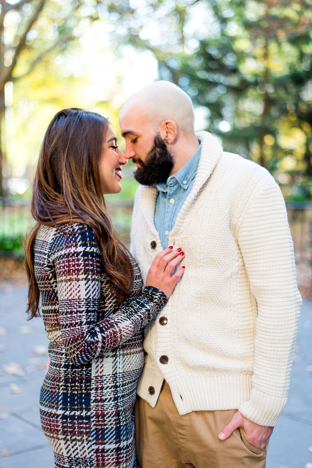 engaged couple is nose-to-nose and smiling for engagement pictures at New York City Hall