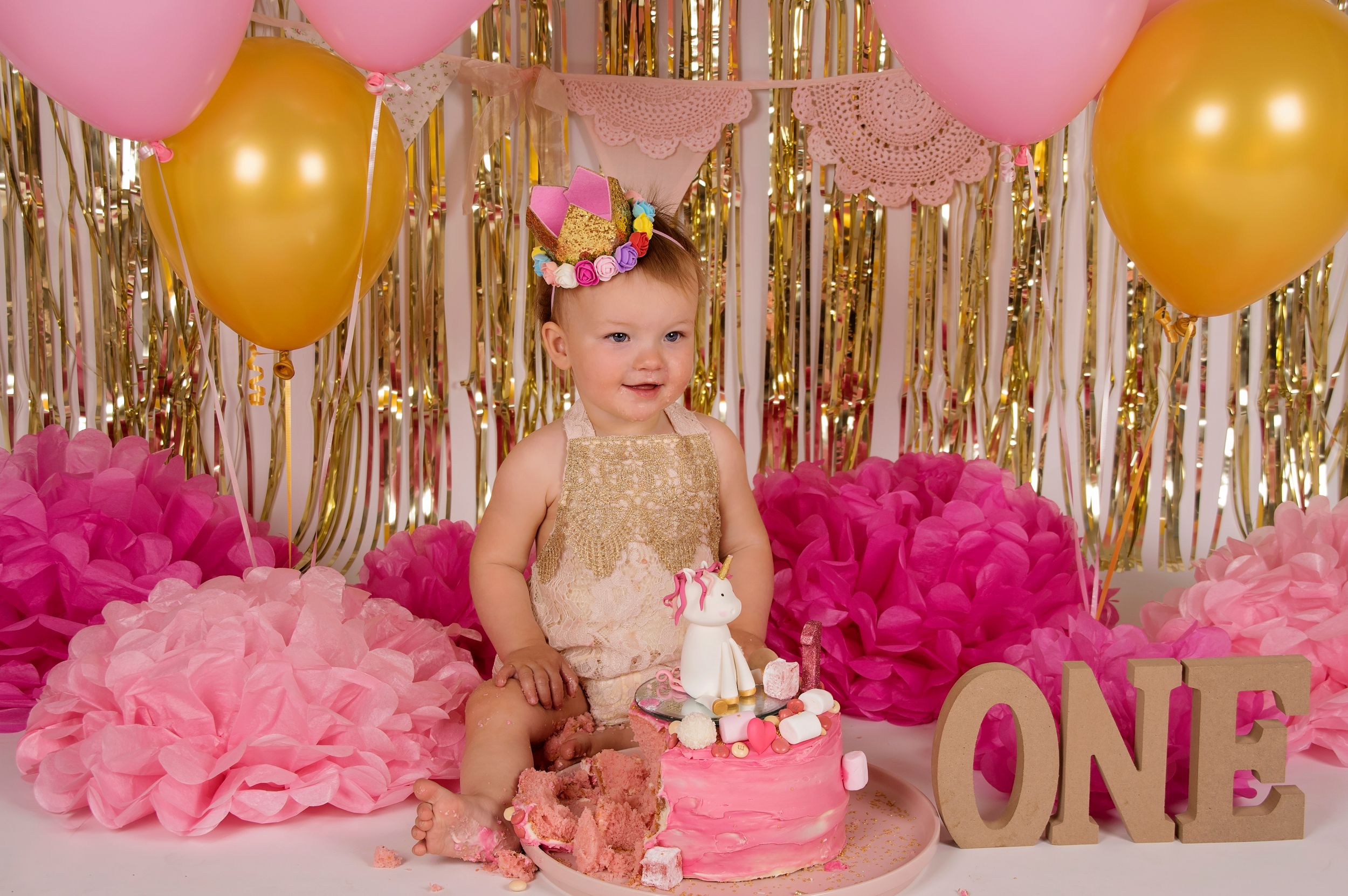 baby girl surrounded by pink decorations with pink cake