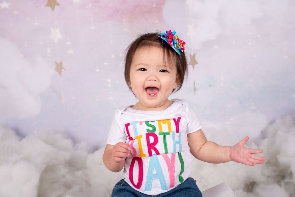 Little Girl laughing during her 1st birthday session with a sky,stars and clouds pastel backdrop