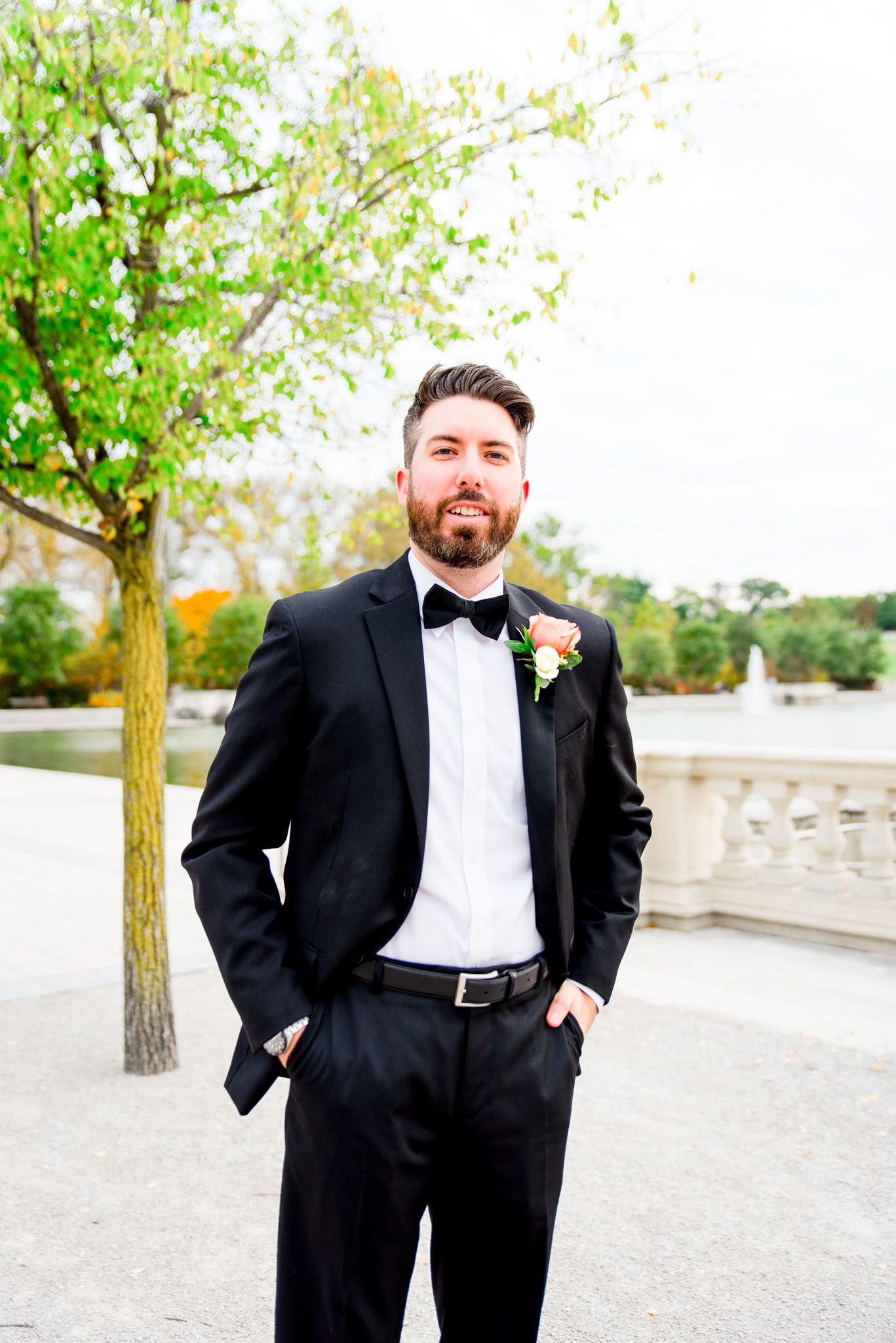 brunette groom with beard in black suit and bowtie smiles off to the side for St. Louis fall wedding at Forest Park