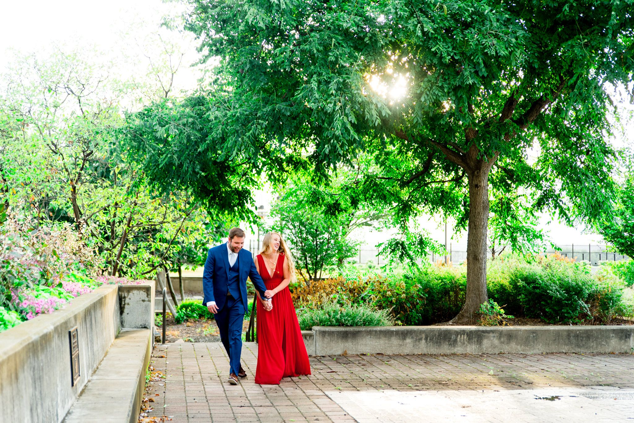 couple in red dress and navy suit walk through park at the Galt House Hotel