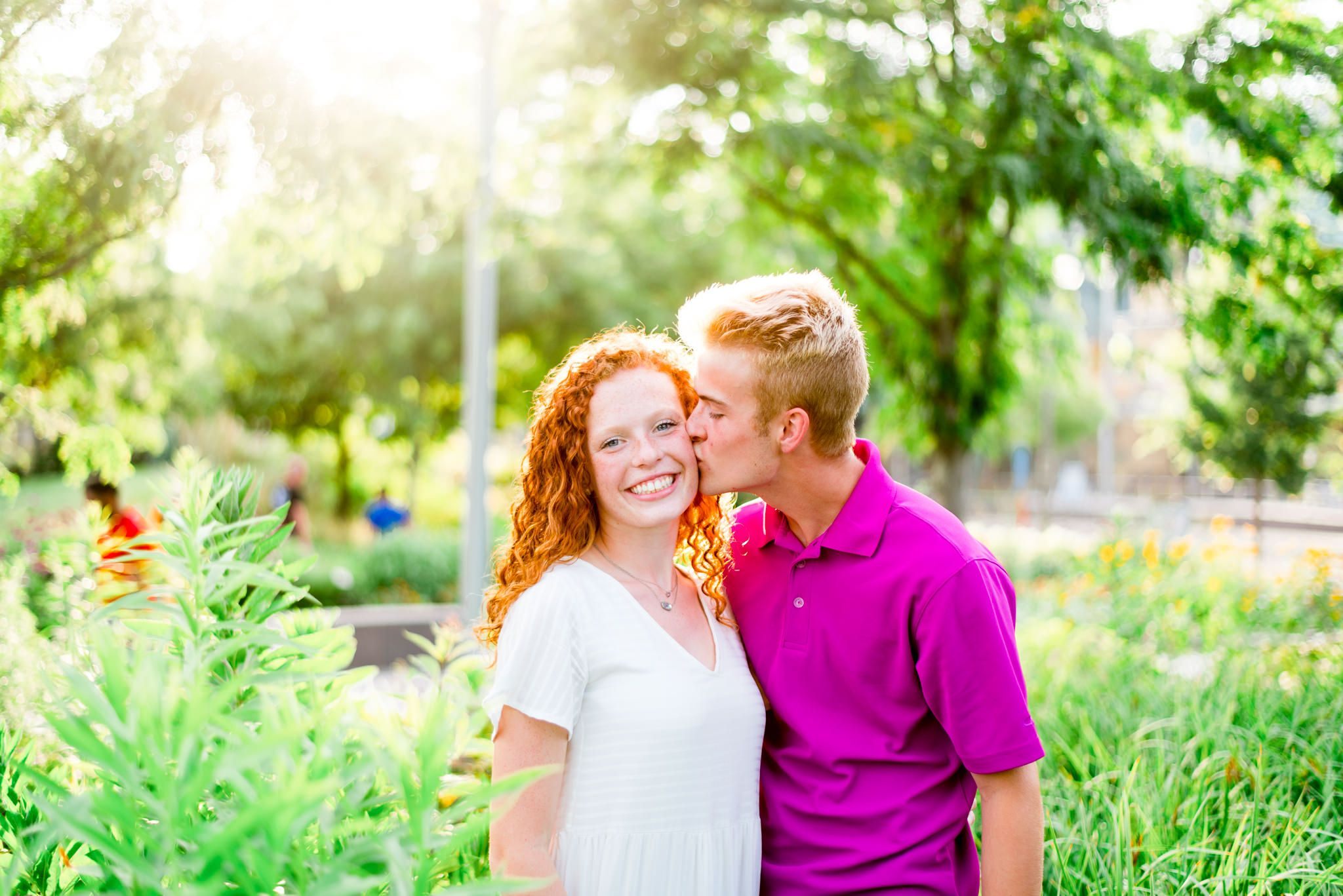 young man kissing young woman with red curly hair on the cheek in the flowers at Smale Park Cincinnati