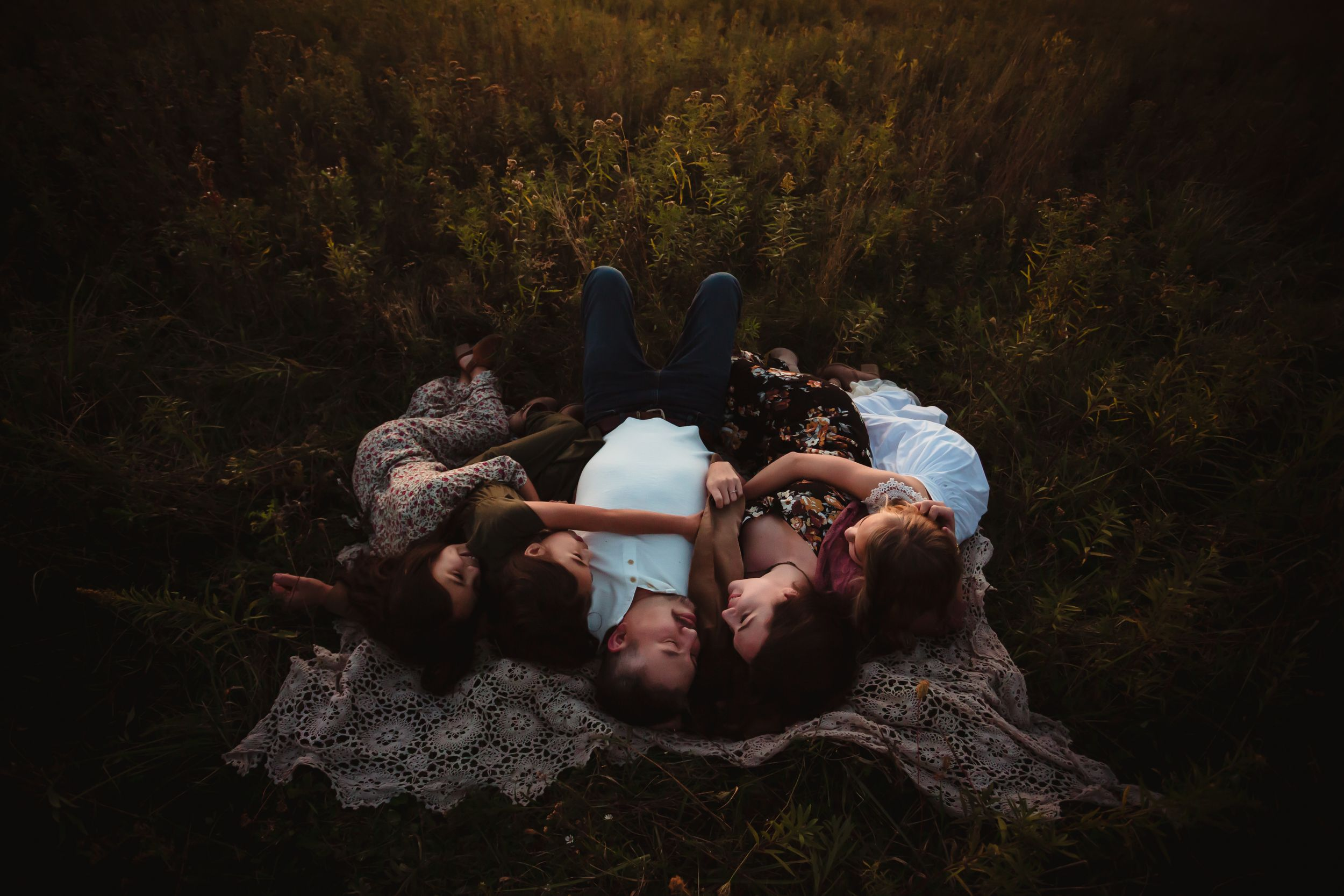 Father, mother, and three daughters lying on a lace blanket in a field embracing each other.
