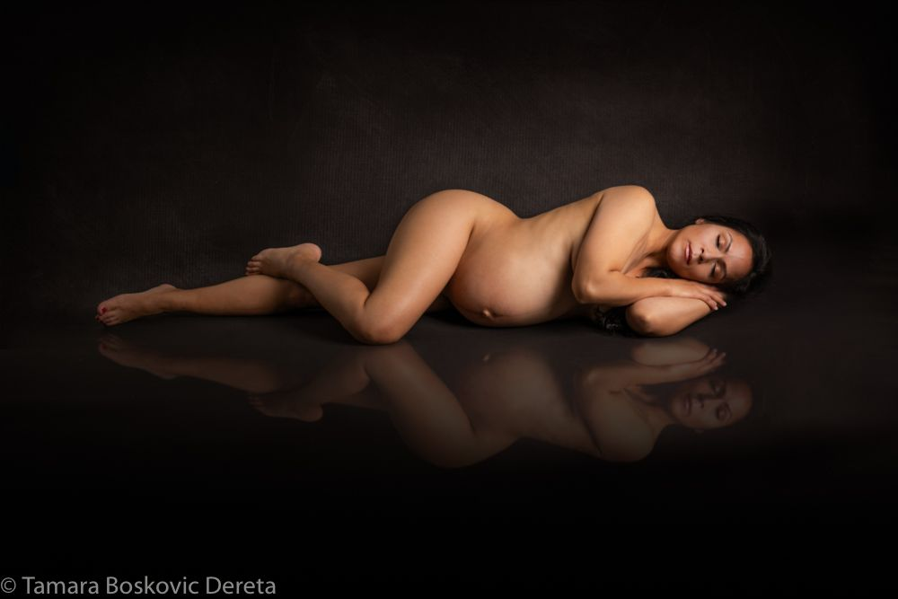 pregnant woman laying down on background with mirror effect