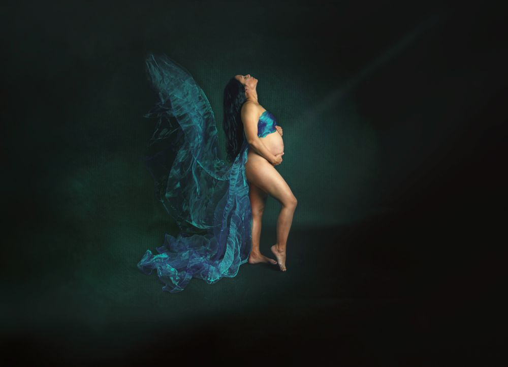 nude pregnant woman covered with blue flying material  that looks like wings