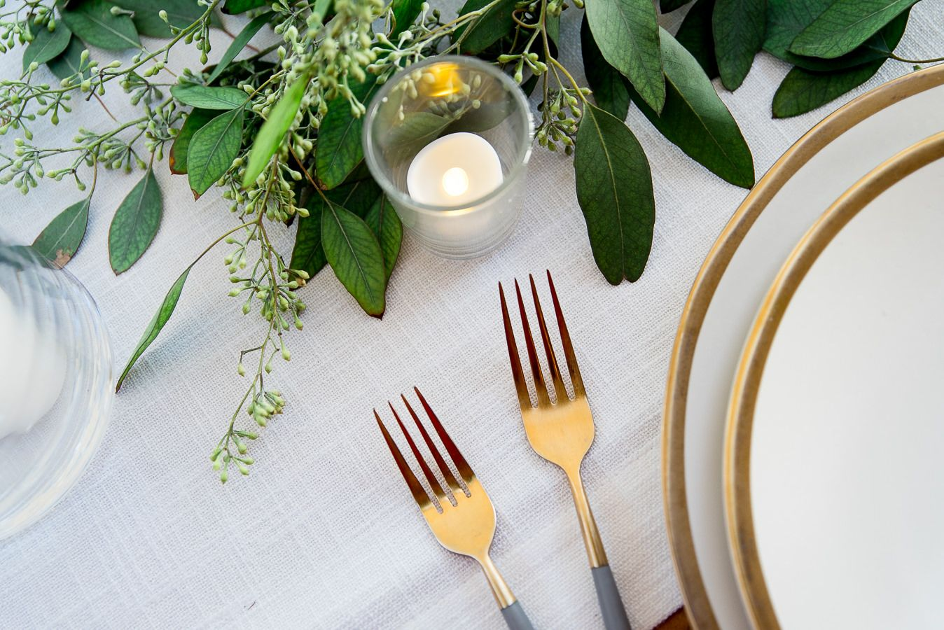 gold forks and plates set with eucalyptus at Pennyroyal Farm outdoor wedding