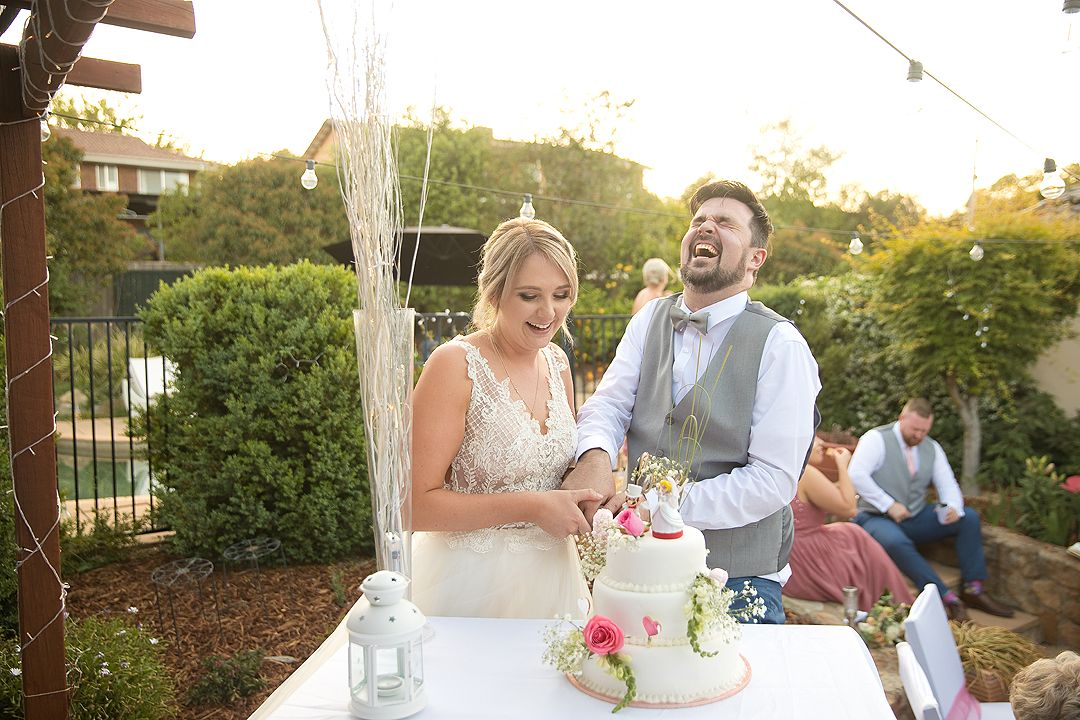 Bride and groom at their wedding reception cutting Mario and Peach cake in Canberra