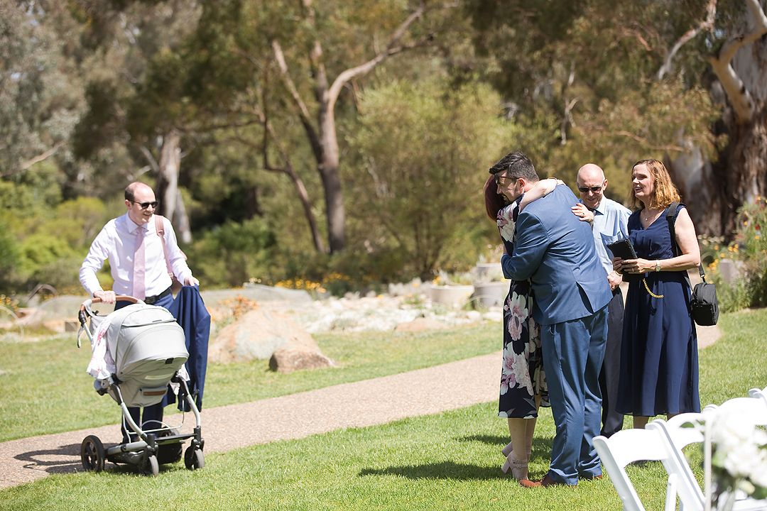 Groom greeting guests at his wedding ceremony at the Rock Lawns of The Australian National Botanic Gardens Canberra