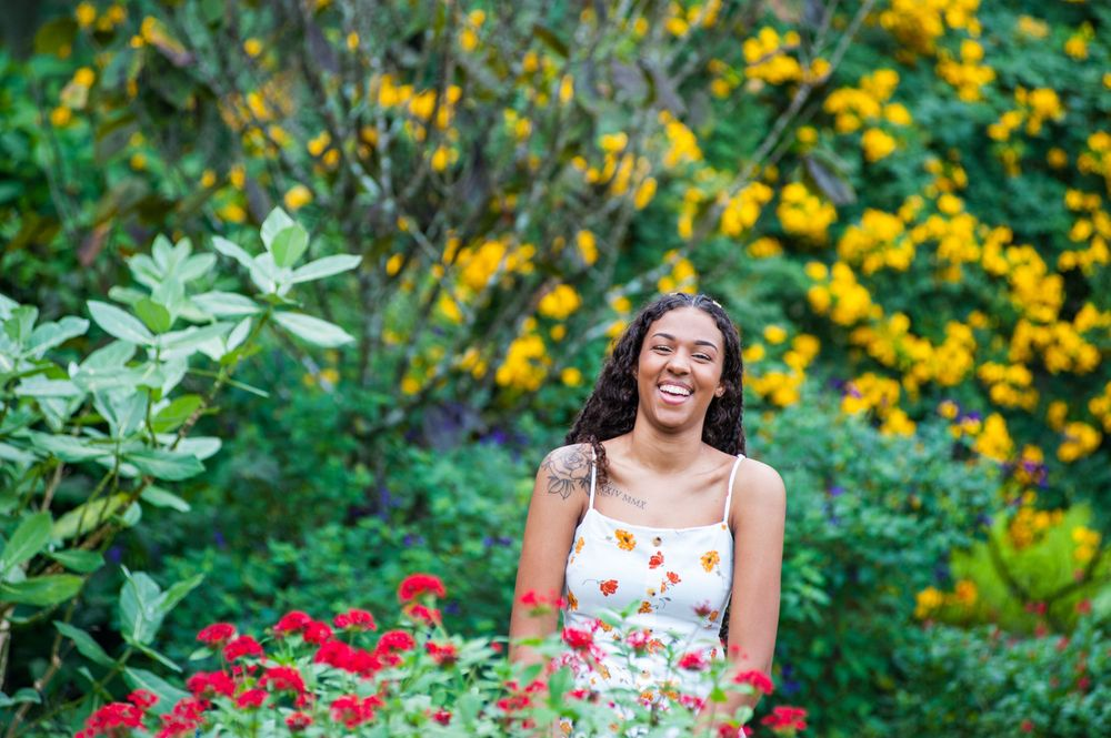 Young woman laughs in a garden of red and yellow flowers