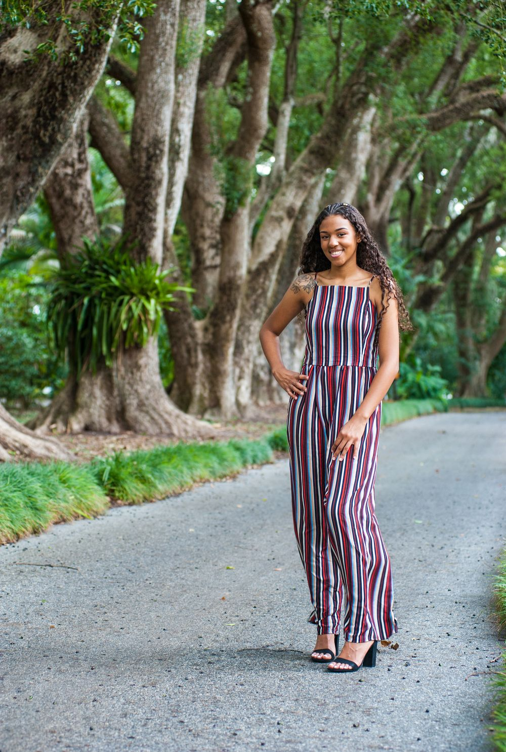 High school senior girl stands amongst camphor trees in a stylish striped jumper