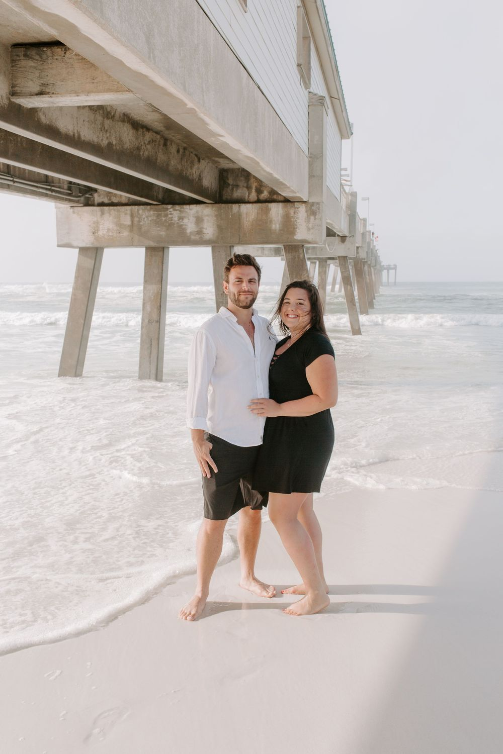 couple standing in front of a pier during their sunrise couples session