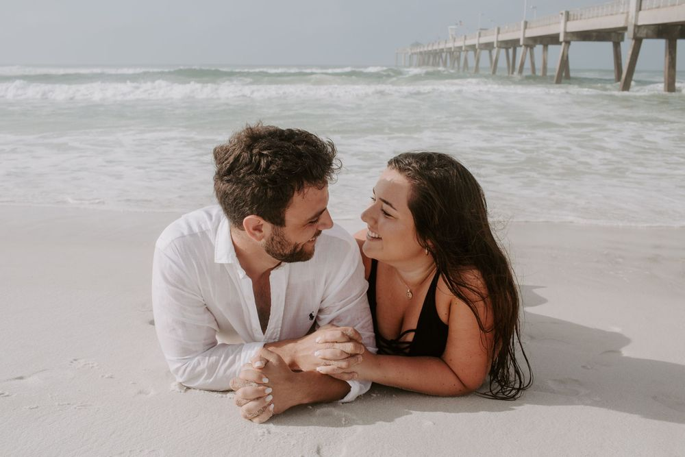 couple laying down on the beach in Destin, Florida looking at each other