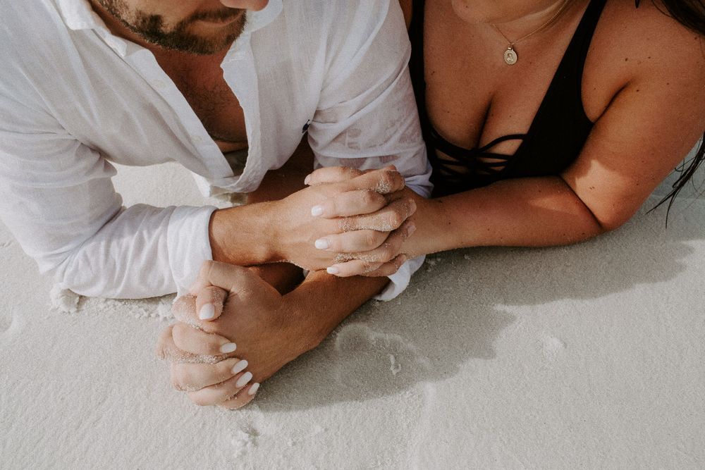 couple holding hands laying on the beach during their couple session in Destin, Florida