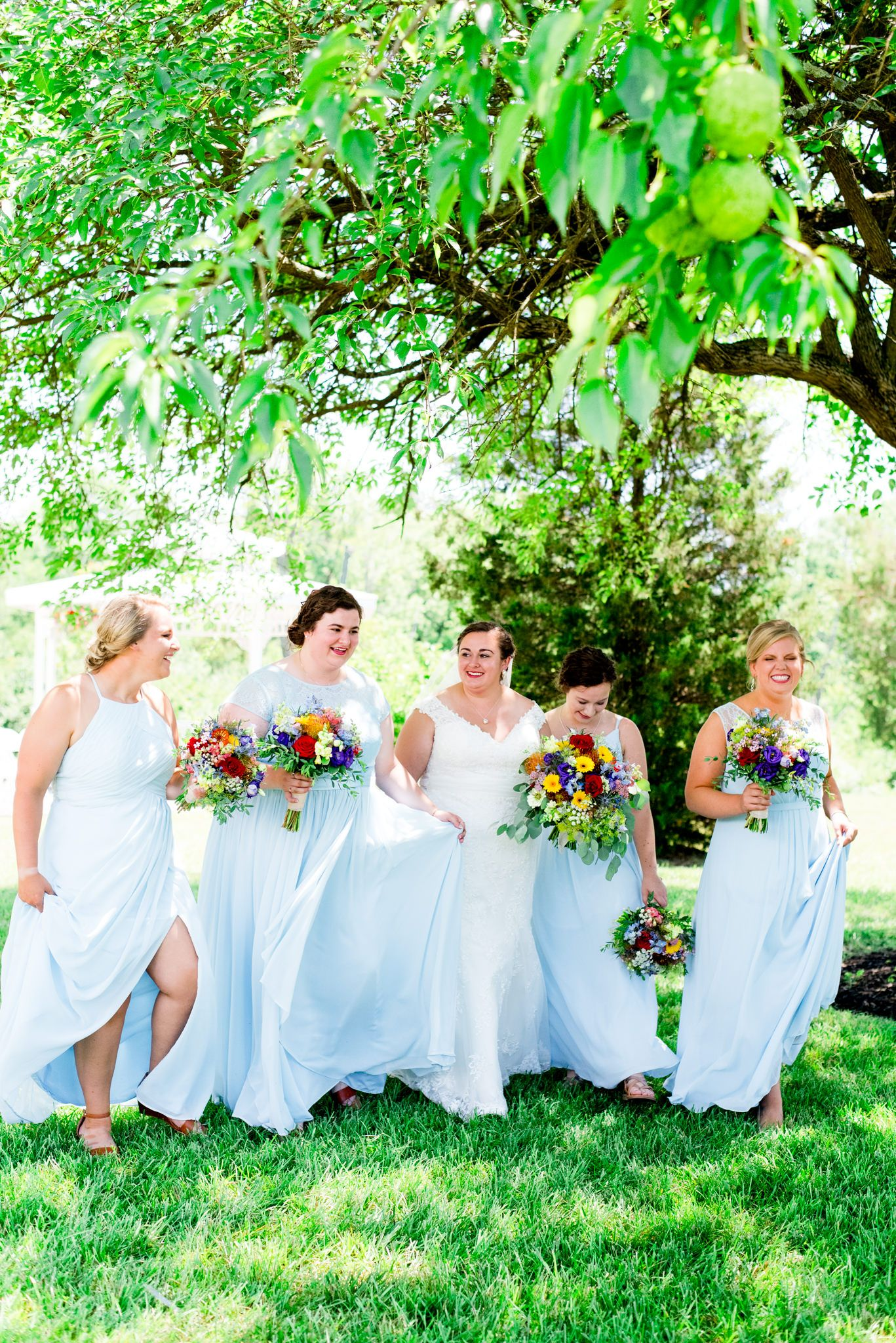 bridesmaids in light blue dresses walk under trees for a colorful outdoor summer wedding in Chicago