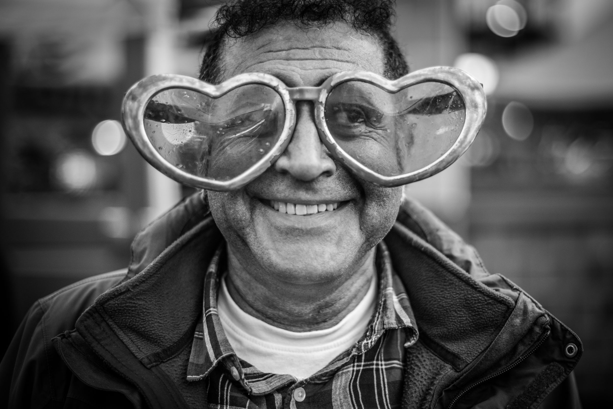 Man wearing oversized heart shaped sunglasses at the Portabello Market in London