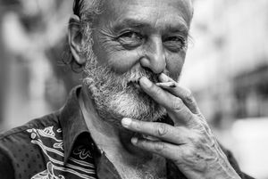 portrait of a Parisian photographer smoking a cigarette with a devilish grin