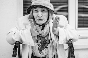 b&w portrait of an elderly Parisian woman sitting in a chair gesturing with hands