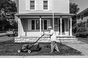 b&w image of an elderly man mowing his lawn