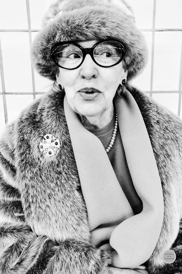 beautiful b&w portrait of an elderly woman in a fur coat, hat and wide rimmed glasses.