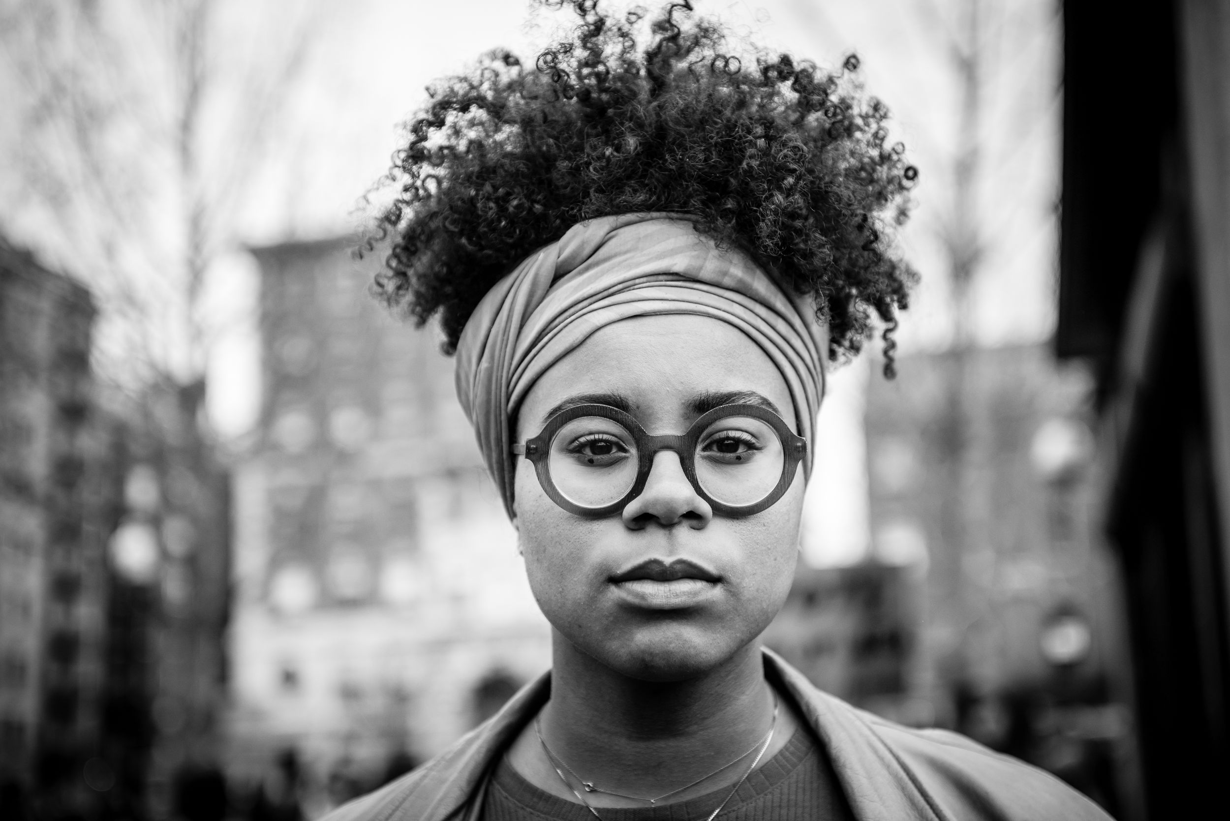 b&w image of a young black woman with afro and wide rimmed glasses