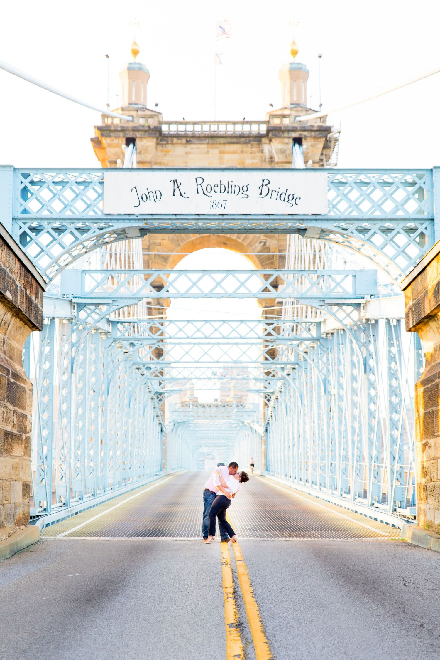 engaged couple kissing and dipping in the middle of blue Cincinnati Roebling Bridge