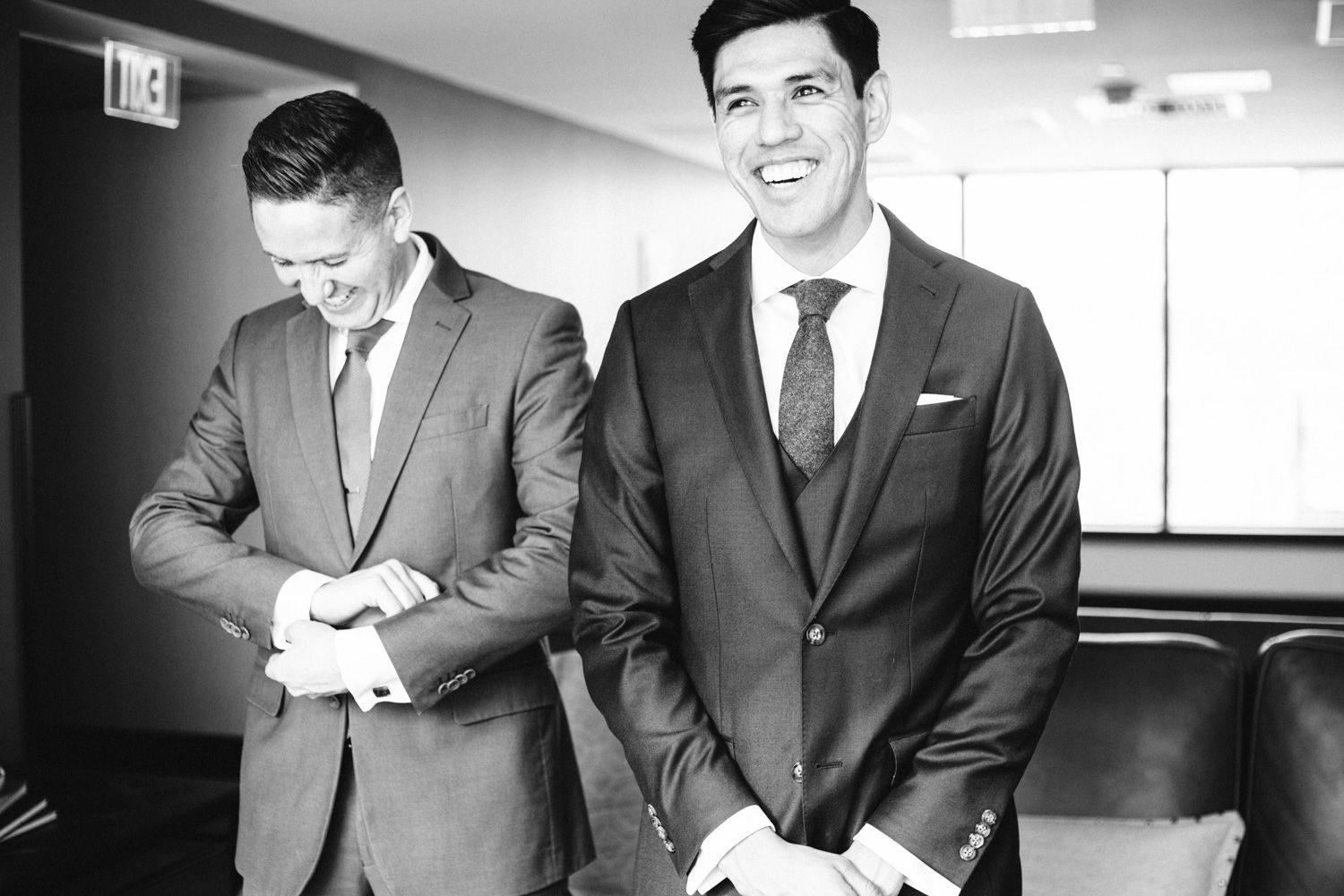 Groom and groomsman share a laugh before a Hudson Valley winter wedding