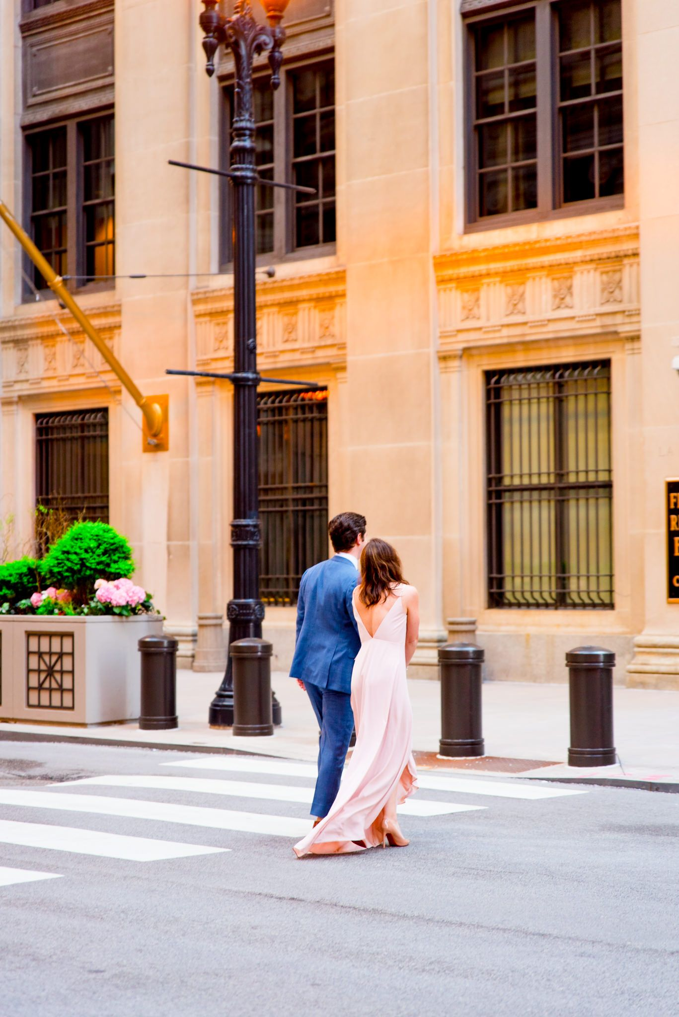 man and woman walk away towards Chicago Board of Trade for sunset engagement pictures in Chicago