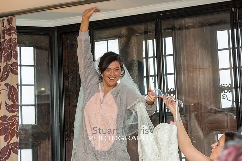 bride stands on a chair puts one hand on the ceiling to steady herself as she passes her wedding dress to a bridesmaid