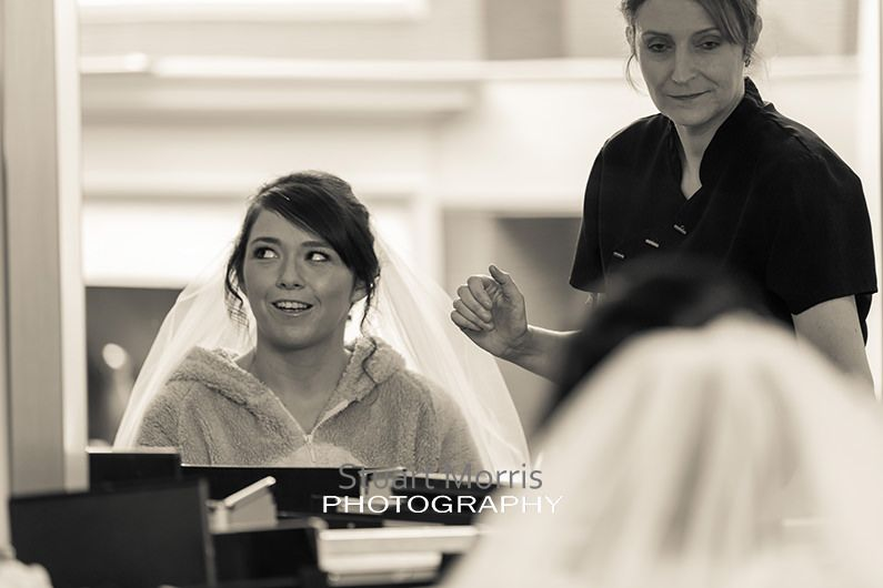 bride looks off to the side reflected in the mirror as she gets her hair and makeup done
