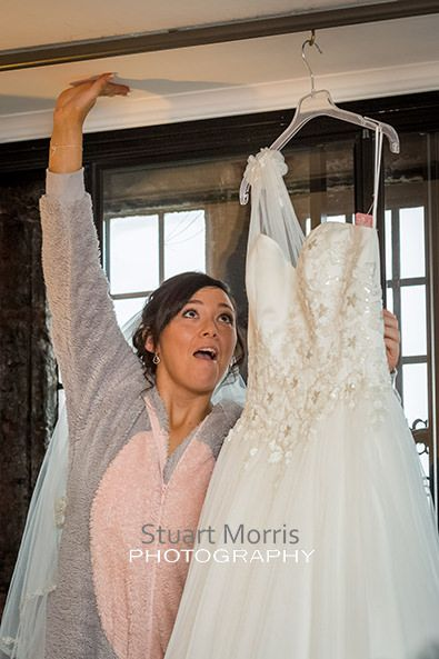 bride in a onesie stretches to reach and lift down her wedding dress hanging in a window at abbey house hotel