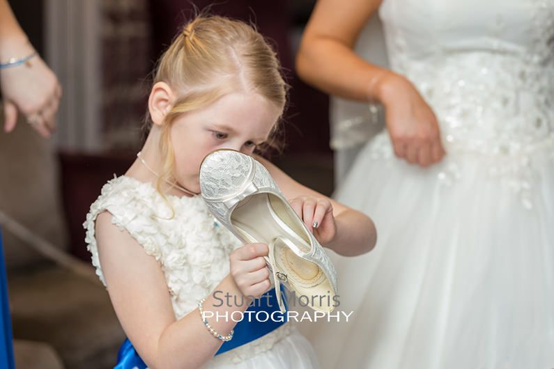 flower girl picks a label off the bottom of the brides shoe during the prep at abbey house barrow in furness