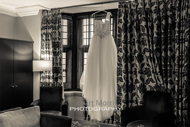 wedding dress hanging in hotel room window at abbey house barrow