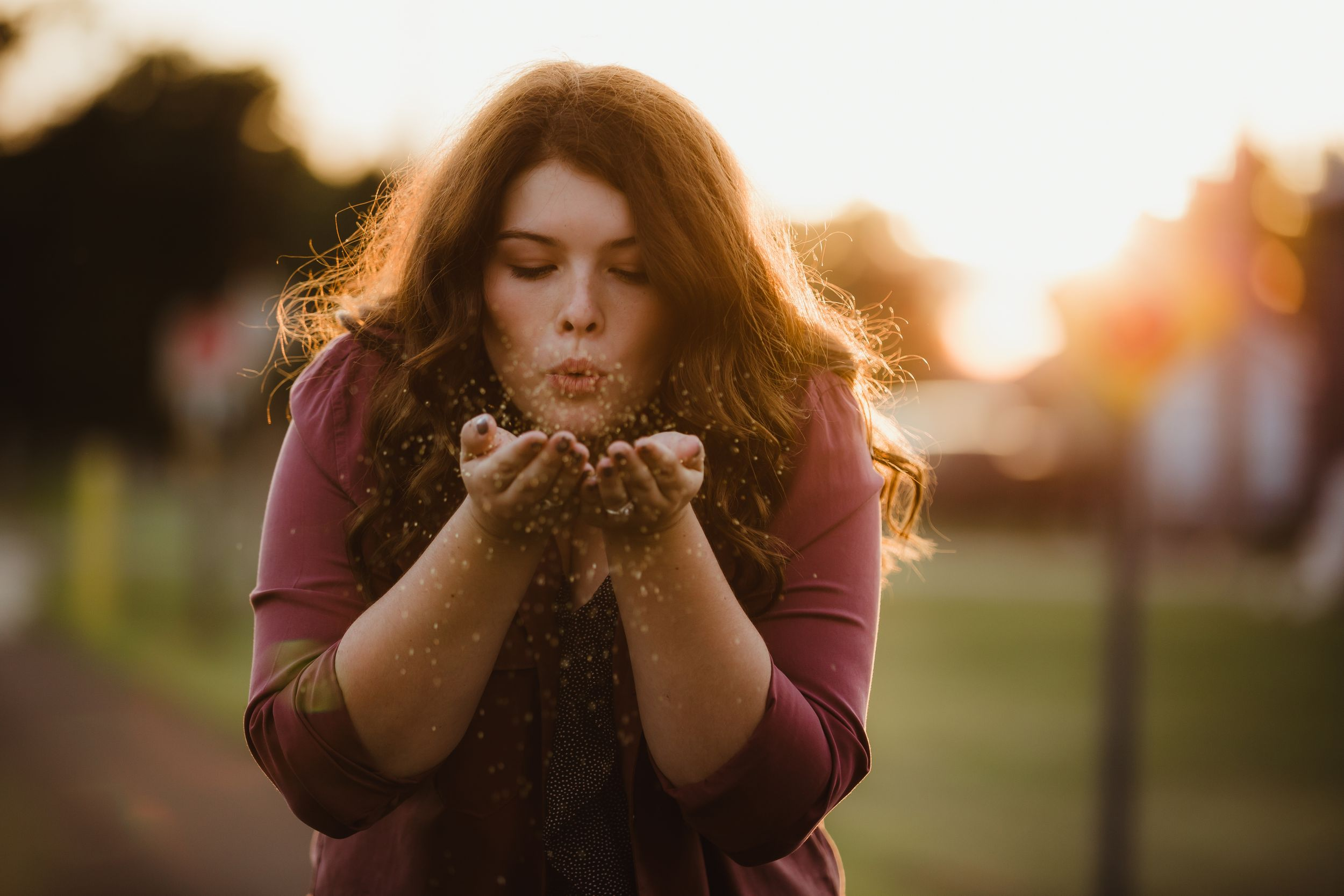 Brunette high school senior photo of a girl blowing glitter with a sunset behind her.