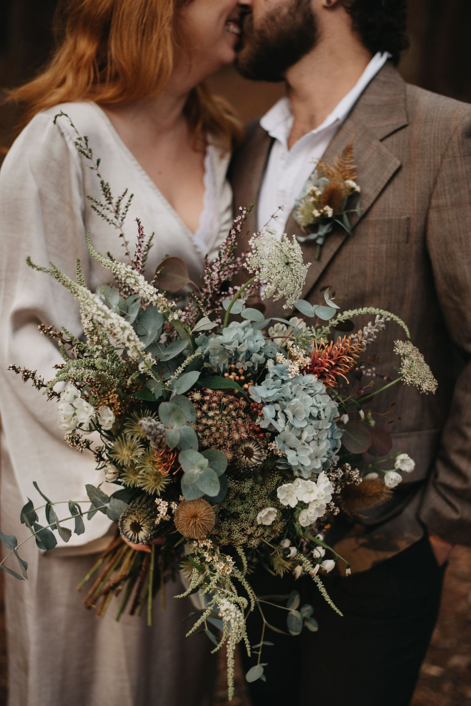 couple kissing with bouquet watagans forest hunter valley nsw