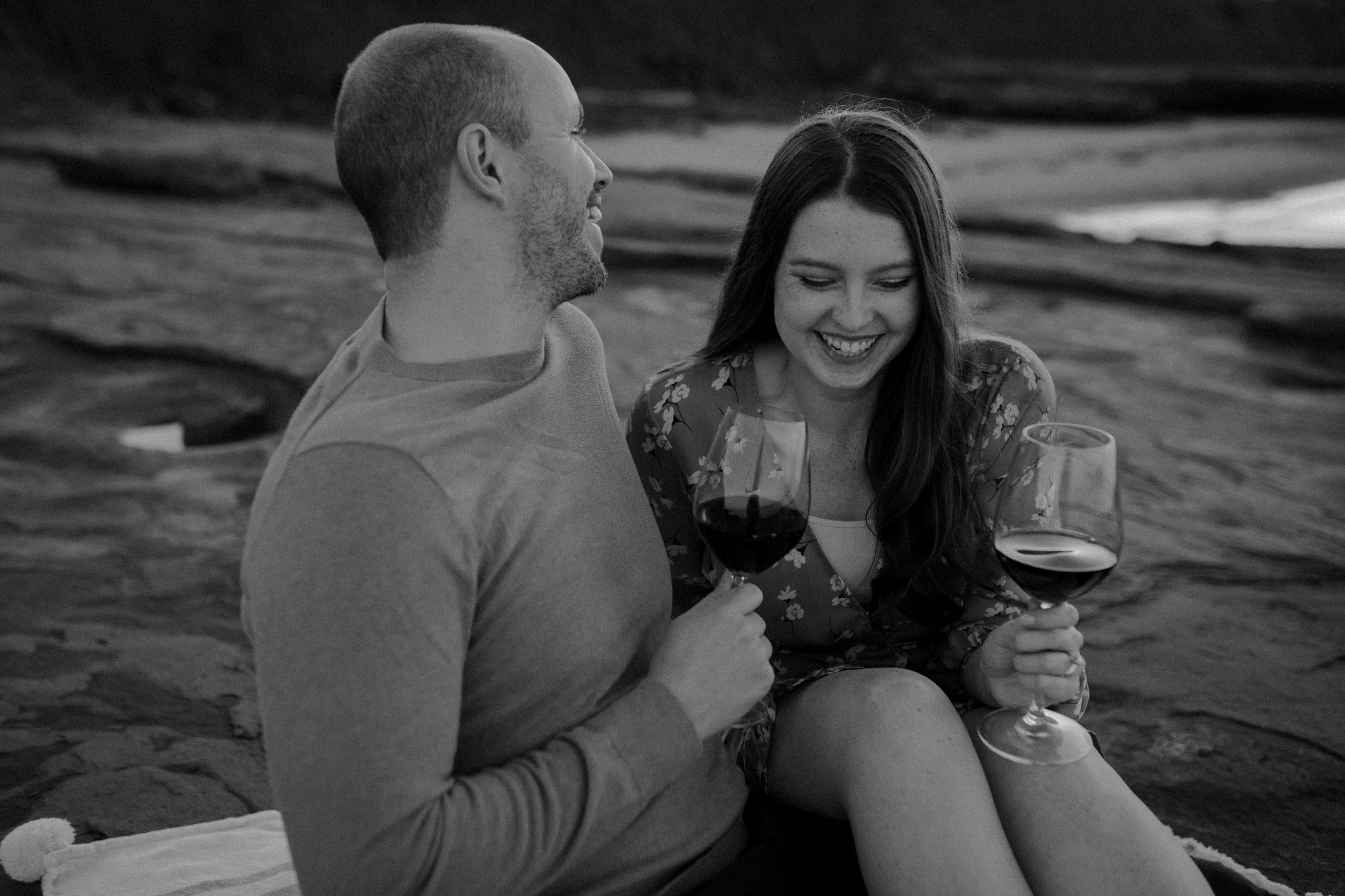 Black and white photo of couple on PEI beach laughing candidly with each other and drinking wine.