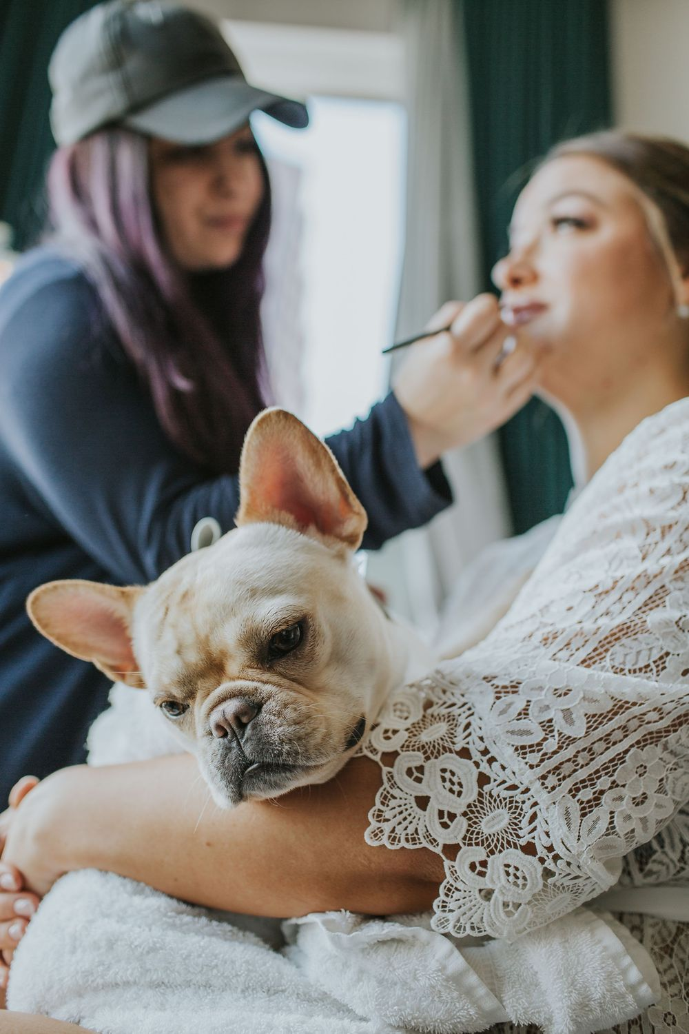 bride holding her dog while getting her makeup done