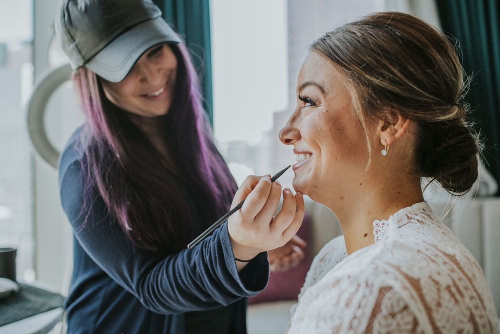 bride smiling while getting her makeup done