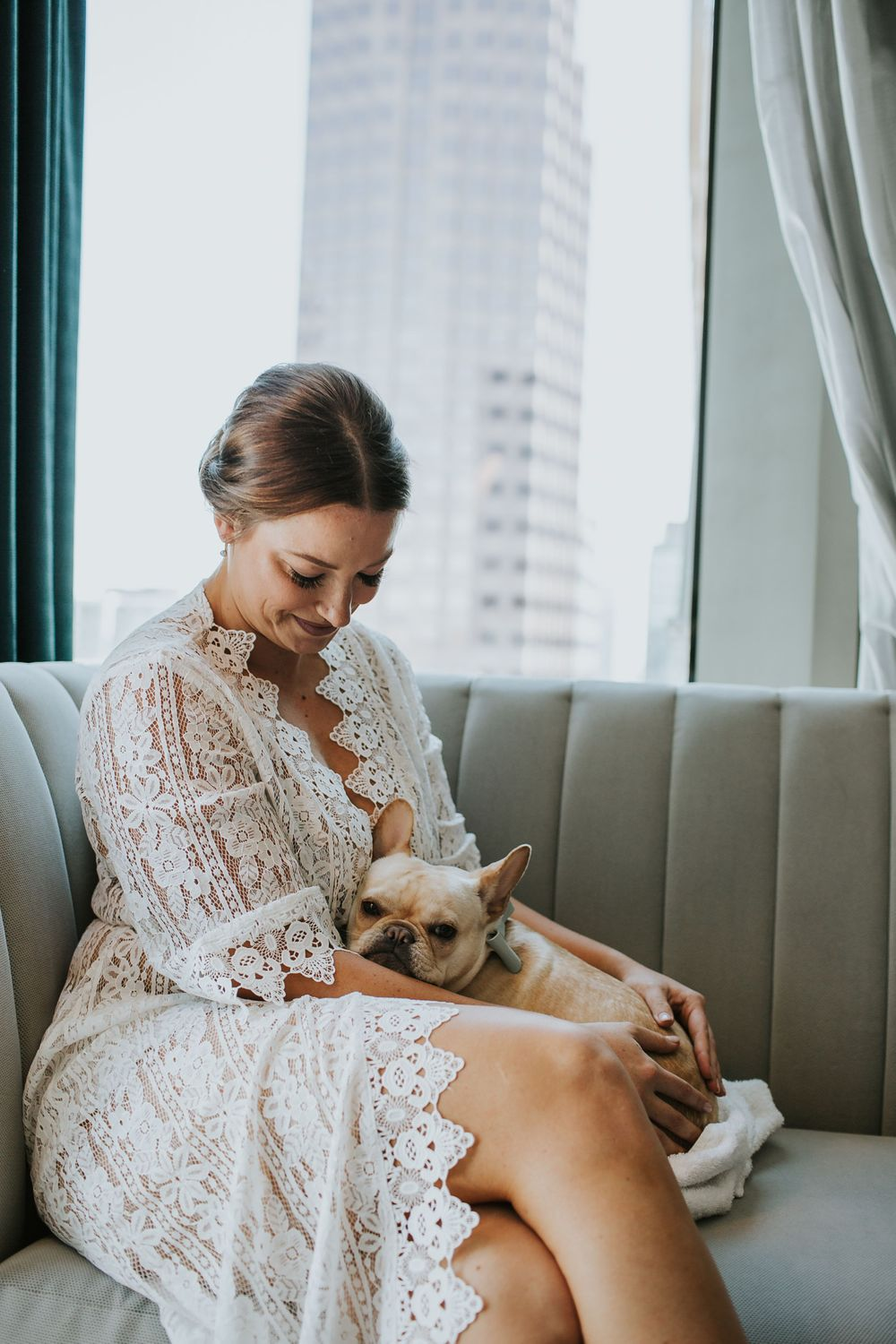 bride cuddling her dog while getting ready