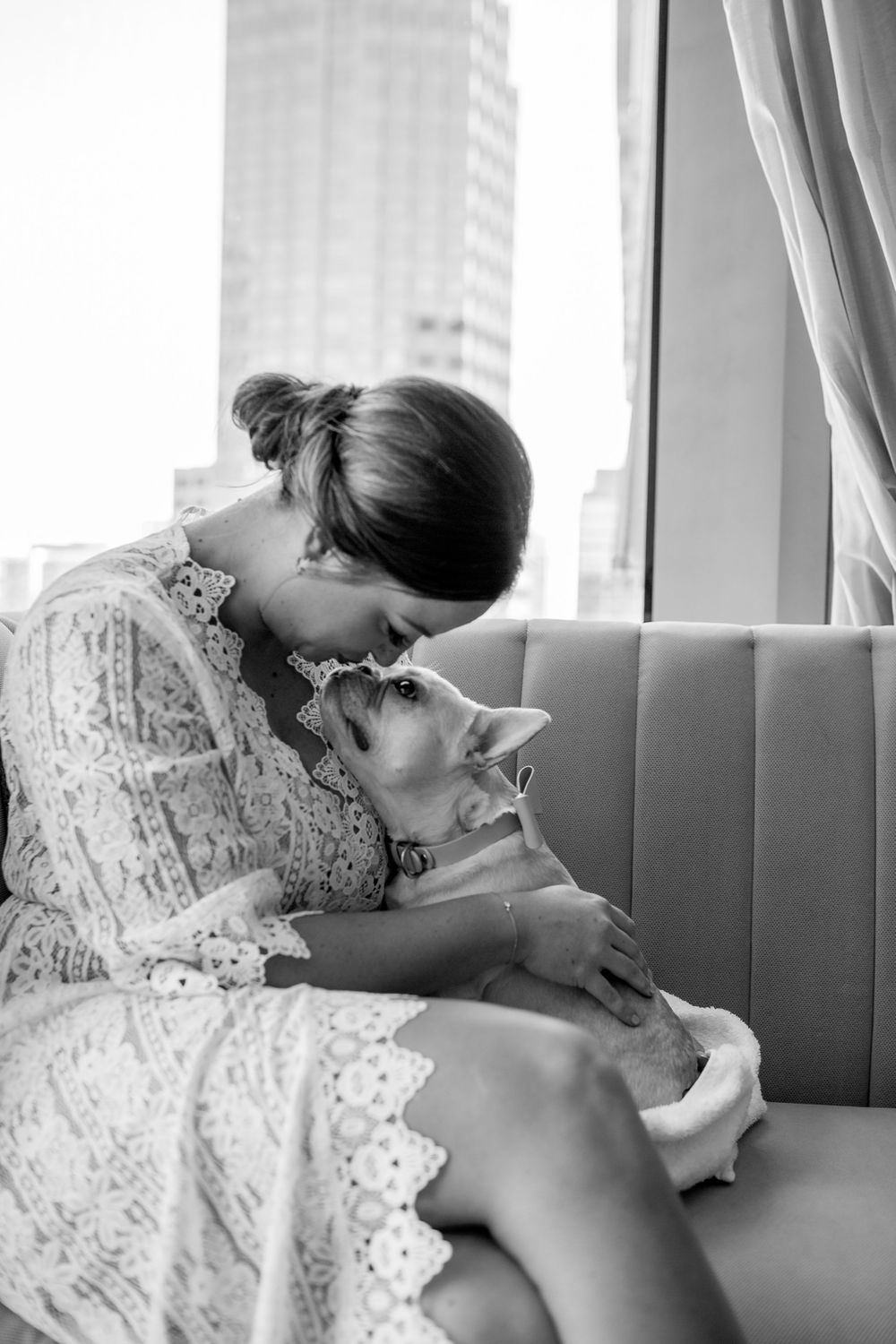 bride kissing and cuddling her dog while getting ready