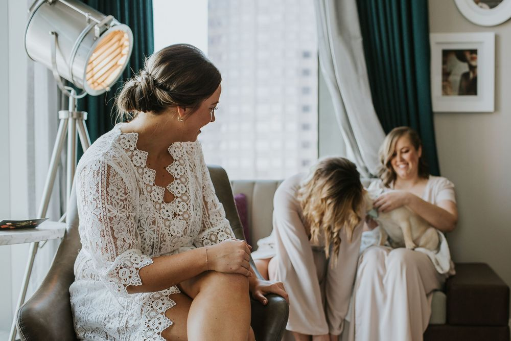bride laughing with her bridesmaids while getting ready