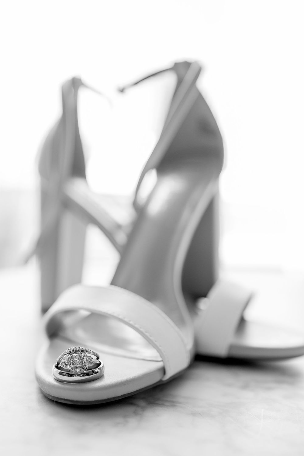 wedding rings sitting in bride's shoes